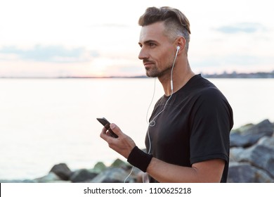 Portrait of a fit sportsman listening to music with earphones and using mobile phone while standing at the beach