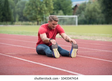 Portrait of Fit and Sporty Young Man Doing Stretching in the Park