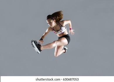 Portrait of fit and sporty young woman jumping on white background.