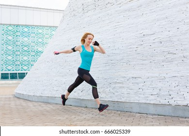 Portrait of fit and sporty young woman doing stretching in city