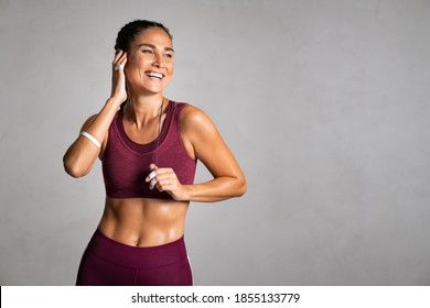 Portrait of fit woman smiling while listenig music with wireless headphones. Laughing fitness middle aged woman with perfect body relaxing after gym training on grey background wall with copy space.