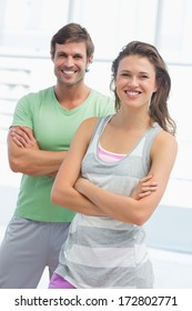 Portrait of a fit young couple standing with arms crossed in bright exercise room