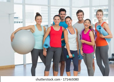 Portrait of fit young people smiling in a bright exercise room