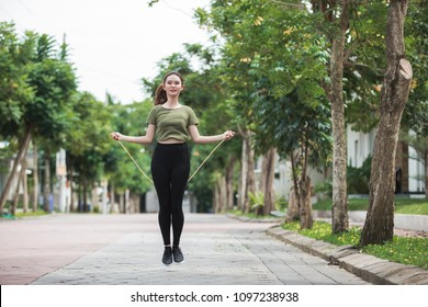 Portrait of fit young woman with jump rope in a park. Fitness female doing skipping workout outdoors