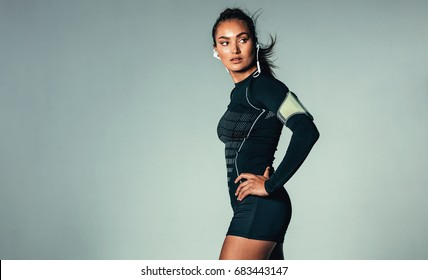 Portrait of fit young woman listening to music on earphones. Healthy muscular woman with arm band over grey background.