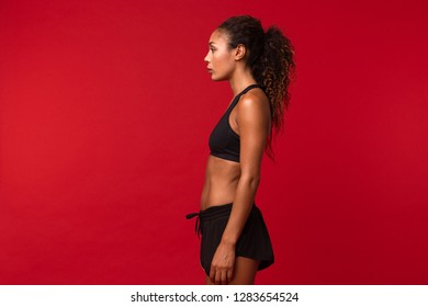 Portrait of fitness african american girl in black sportswear standing isolated over red background