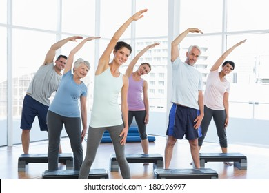 Portrait of fitness class stretching hands in yoga class