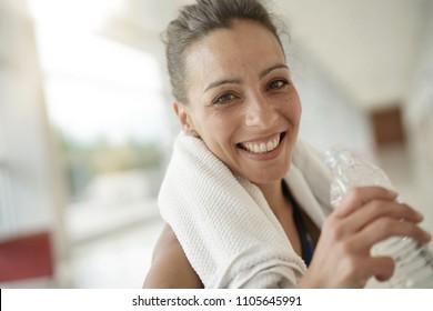Portrait of fitness girl drinking water from bottle
