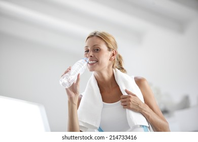 Portrait of fitness girl drinking water from bottle