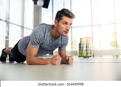 Portrait of a fitness man doing planking exercise in gym