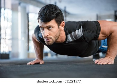Portrait of a fitness man doing push ups in gym