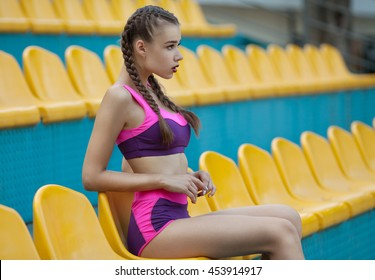 Portrait of a fitness with tennis racket woman resting at outdoor stadium.