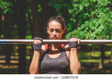 Portrait of fitness woman doing pullups in nature.