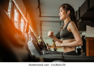 Portrait of Fitness woman running on treadmill in gym listening to music.exercising concept.fitness and healthy lifestyle.