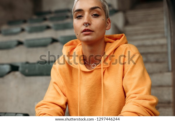 Portrait of a fitness woman sitting in the stands of a stadium. Close up of a woman sitting on the stairs inside a stadium.