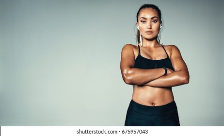 Portrait of fitness woman standing with her arms crossed. Female model in sportswear over grey background.
