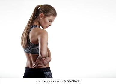 Portrait of fitness woman suffering from hip pain over grey background with copy space for text.