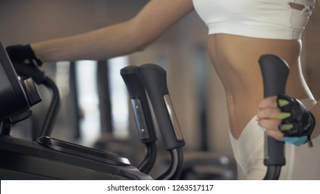 Portrait fitness woman warm up before training on elliptical cross trainer