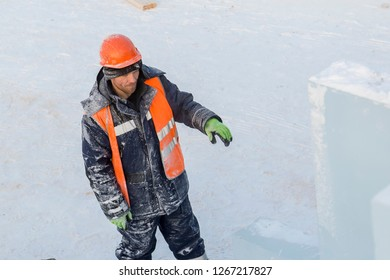 Portrait of a fitter slinger in a jacket and helmet on the unloading of ice plates