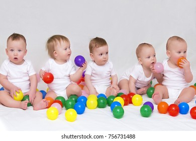 Portrait of five cute babies on light background playing with colorful balls.
