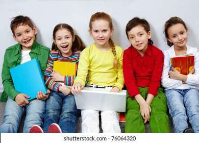 Portrait of five pupils looking at camera while sitting on the floor