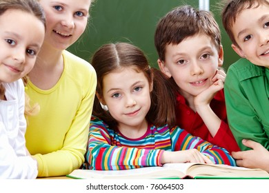 Portrait of five pupils looking at camera with open book near by