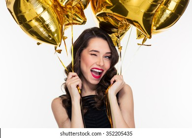 Portrait of flirty attractive winking curly retro styled woman with golden balloons
