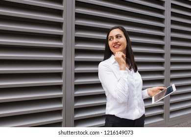 Portrait of flirty businesswoman with pc tablet looking away. Young Caucasian female student standing with digital tablet outdoors. Businesswoman concept