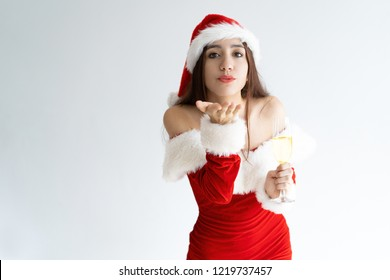 Portrait of flirty young woman with champagne flute sending kiss. Mixed race girl wearing Santa Claus outfit congratulating with New Year. Christmas and New Year concept