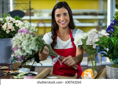 Portrait of a florist offering flowers at the counter in the florist shop
