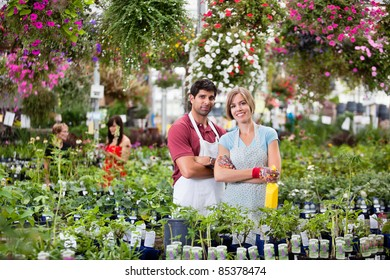 Portrait of florists at greenhouse with people in background