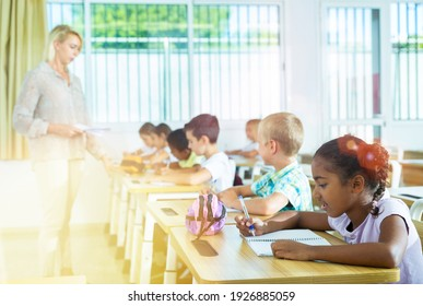Portrait of focused aframerican preteen schoolgirl writing exercises in workbook in classroom during lesson