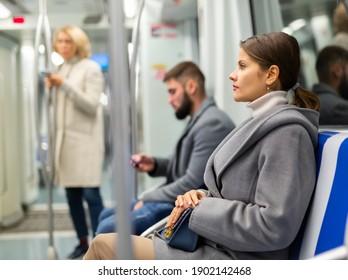 Portrait of focused brunette wearing light overcoat during trip in metro train ..