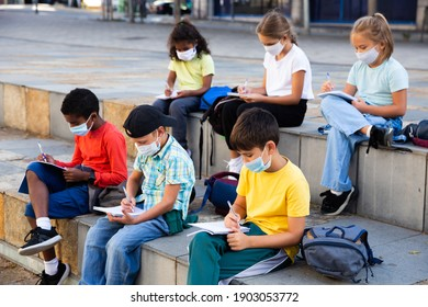 Portrait of focused diligent schoolchildren in face masks during lesson outside school in warm autumn day. New lifestyle in coronavirus pandemic
