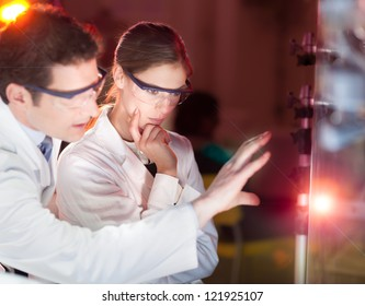 Portrait of a focused electrical engineering researchers in their working environment checking the phenomenon of breaking laser beam on the glass surface.