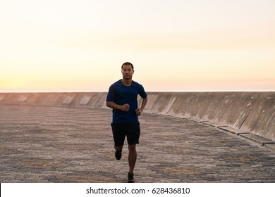 Portrait of a focused and fit young Asian man in sportswear running alone along a boardwalk outside in the early morning