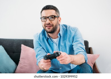 portrait of focused man playing video game at home