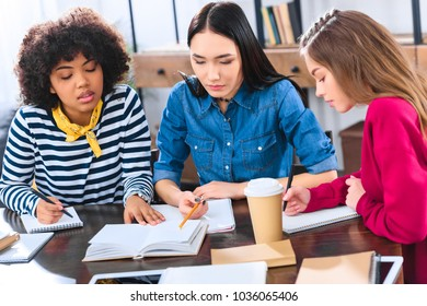 portrait of focused multiracial students doing homework together