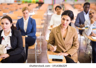 Portrait of focused people of different nationalities during business seminar in conference hall