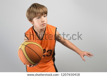 1c999c37534 Portrait of a focused serious attentive little basketball player in orange  sportswear holding the ball.