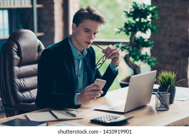 Portrait focused serious concentrated banker hold hand use user modern technology look news pensive ponder sit desk table chair thoughtful black stylish trendy jacket interior industrial studio