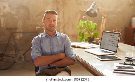 Portrait of a focused young businessman sitting with his arms crossed at a desk in a trendy office
