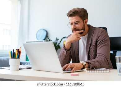 Portrait of focused young startup entrepreneur working with laptop in home office