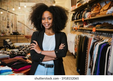Portrait with folded arms a young beautiful owner of clothes shop at entrance of commercial activity - Millennial starts a new start-up activities in her city - Sales assistant waits for customers