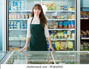 Portrait of food store employee near shelves with products