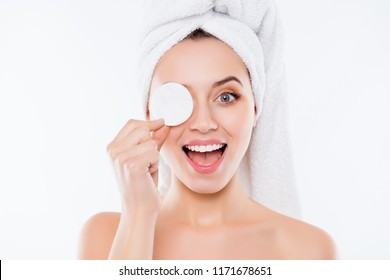 Portrait of foolish playful woman using sponge for application of lotion close one eye with cotton keeping open mouth with towel on head isolated on white background