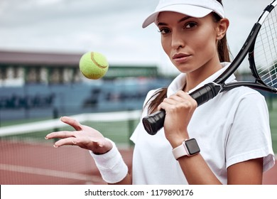 Portrait of forceful woman playing tennis in indoor court, focus on tennis racket hitting ball, copy space