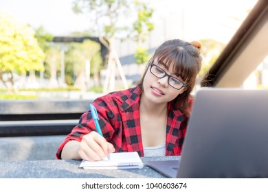 Portrait foreign or foreigner student: Attractive woman is using pen for writing note on notebook while open laptop. Charming beautiful girl is university student. She get scholarship from her country
