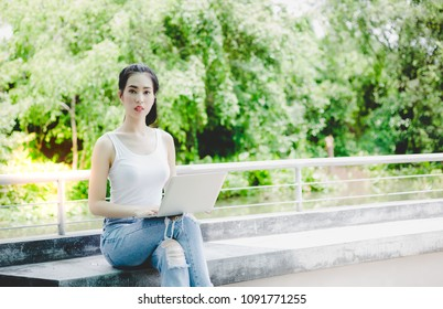 Portrait foreigner student: Attractive woman use laptop computer for working or checking information. Charming beautiful girl is university student. Young girl is foreigner student. copy space