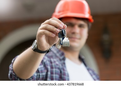 Portrait of foreman in hardhat giving keys of new house